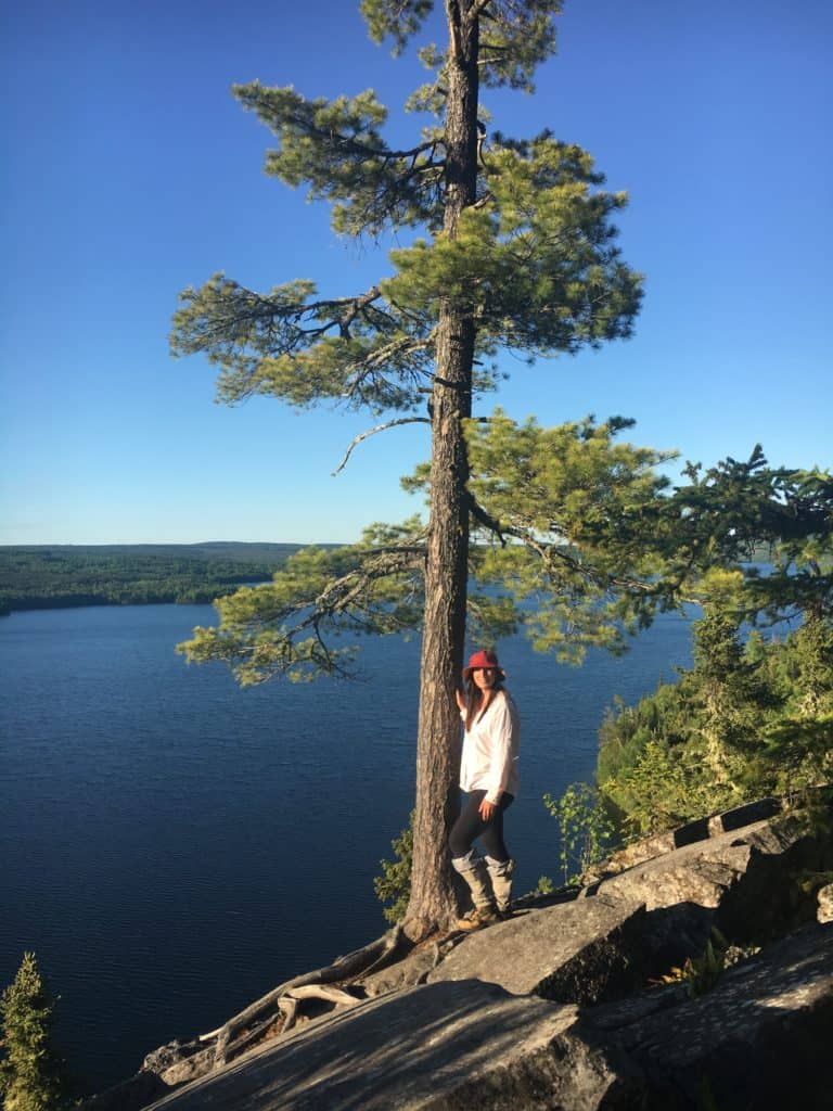 Boundary Waters Podcast host Chelsea posing next to a tree in the Boundary Water Canoe Area Wilderness